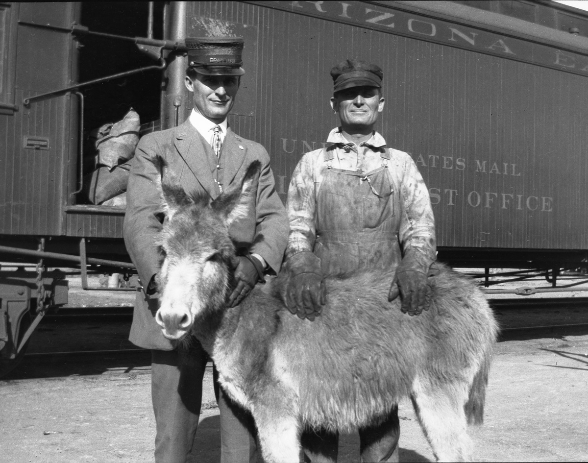 Two railroad workers with a donkey.